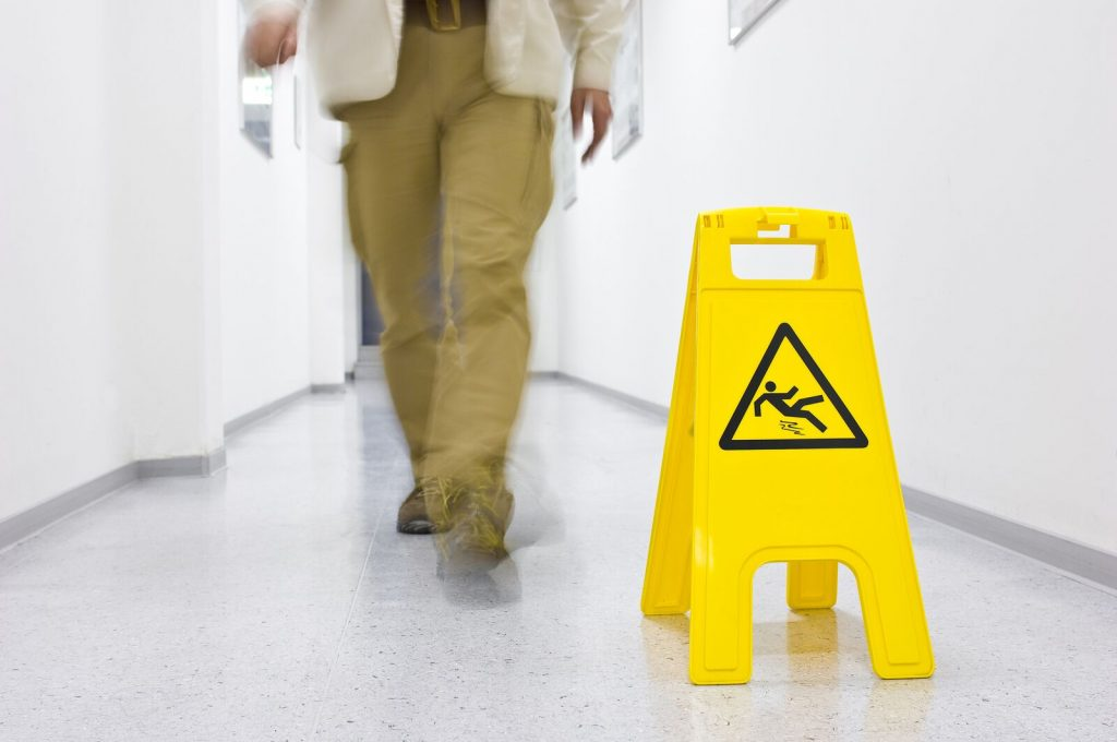 Picture of Man Walking Down Hallway With Wet Floor Sign