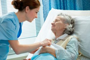 Picture of Elderly Woman With Nurse in Hospital Bed